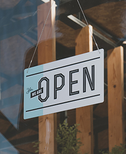 open sign through window of business